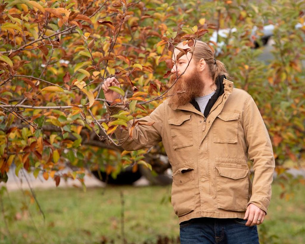 Sam Fitz, co-founder of ANXO cider in Washington D.C., inspects the orchard.