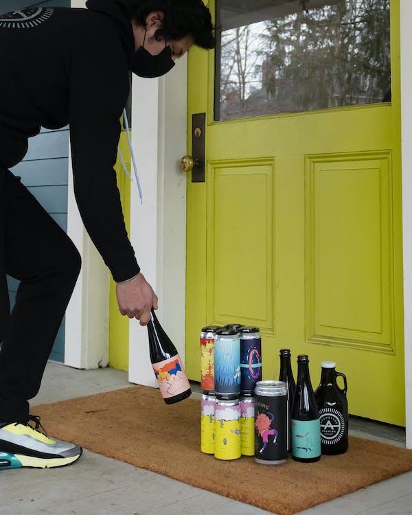person delivering beer, welcome mat, front door