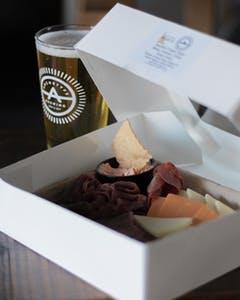 Photo of a beer in an Archetype logo'd glass, next to a box of charcuterie prepared by South Slope Cheese Company