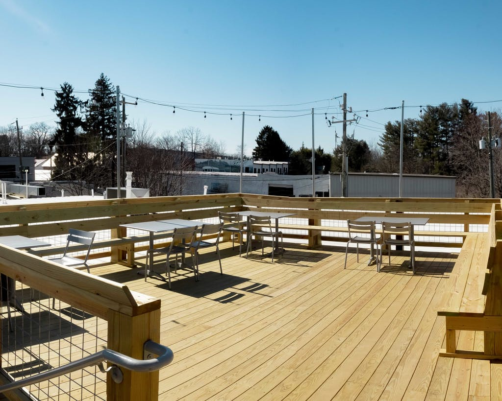 wooden rooftop deck with tables and chairs
