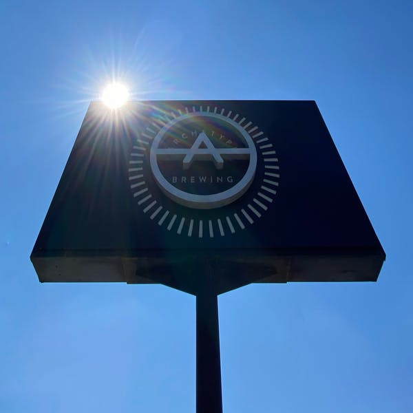 Archetype Brewing Sign with sun and blue skies