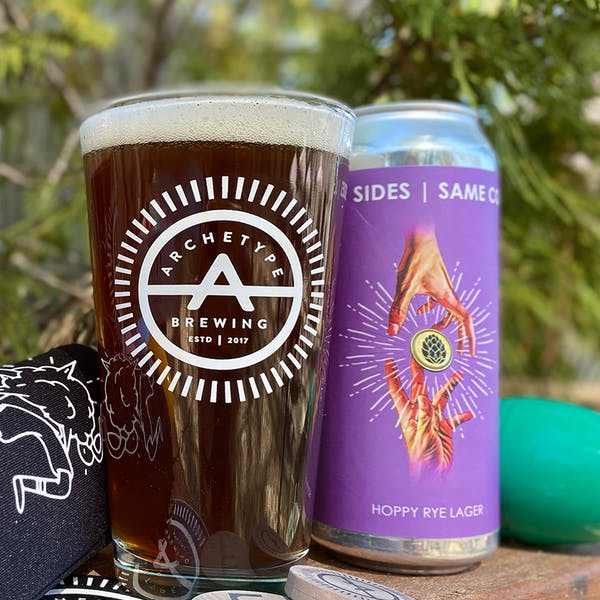 Archetype pint glass with dark beer next to purple can