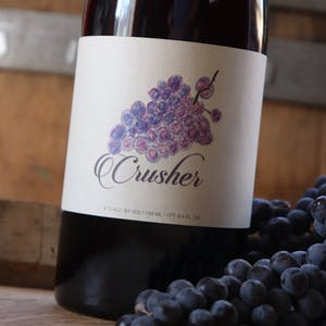 Close up image of Crusher next to Merlot Grapes on a wine barrel