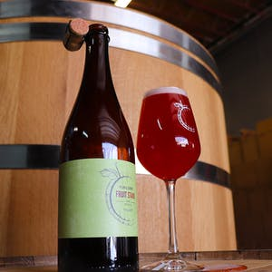 Casey Brewing and Blending's Plum and Cherry Fruit Stand on barrel in front of a Foeder