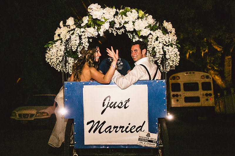 Couple waves at guests as they depart in a pedicab that reads Just Married