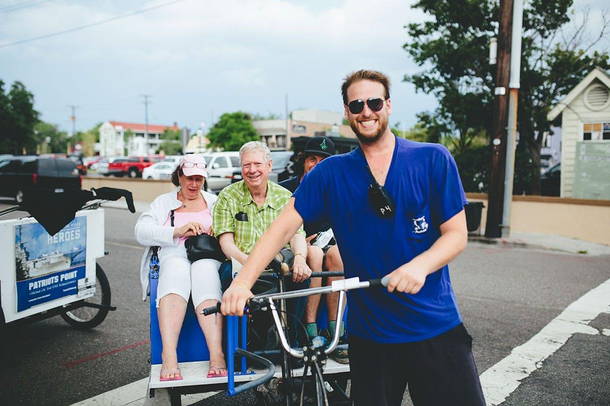 Pedicab driver and passengers smile at camera