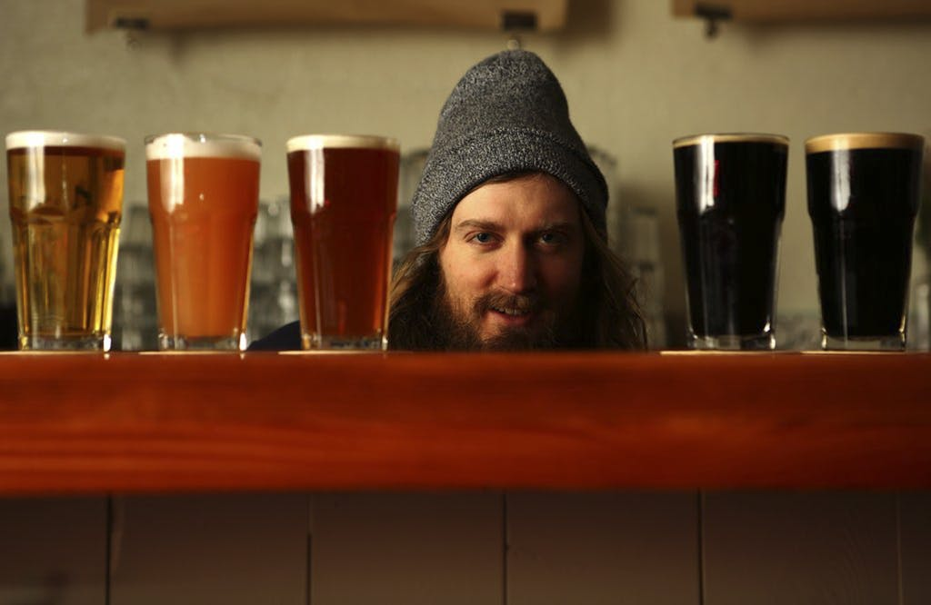 teve Luke, owner of Cloudburst Brewing, with a beer selection at his tasting room's bar,