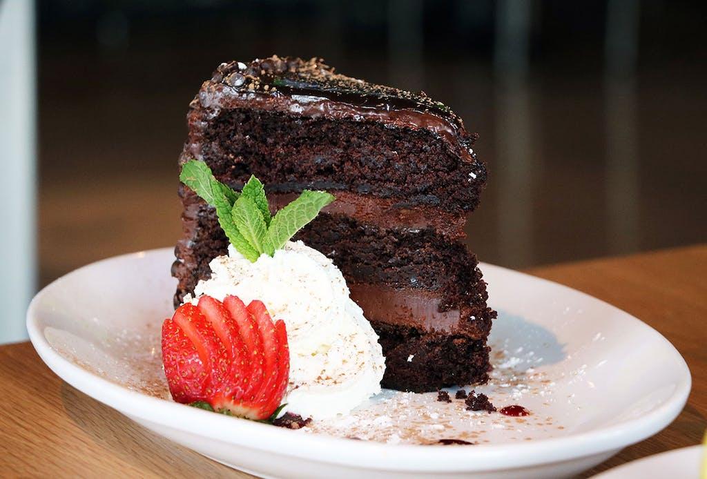 Three layer chocolate fudge cake topped with fresh whipped cream and raspberry puree