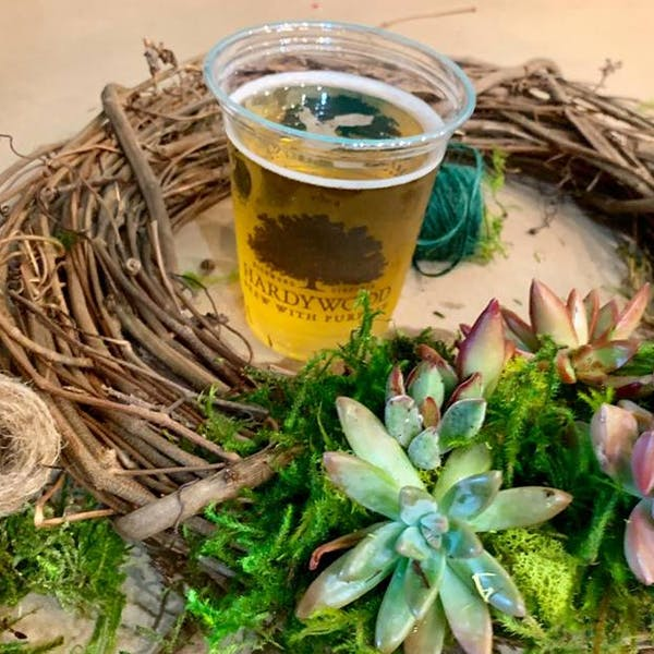 spring wreath workshop photo with wreath and succulents and a beer