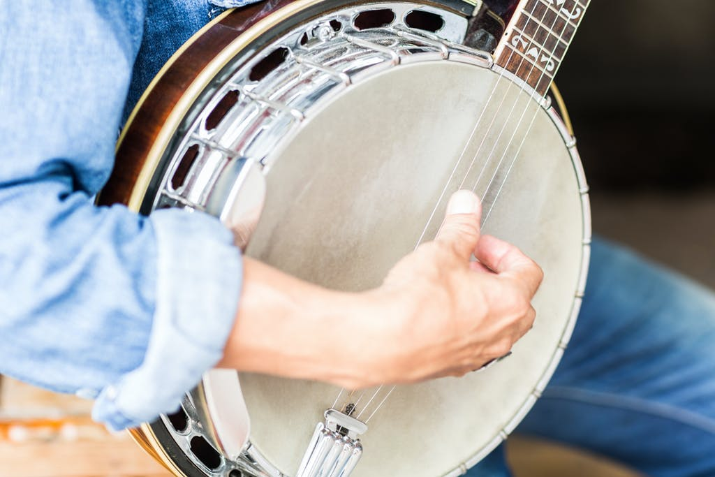 Closeup shot of a man's hand strumming on a banjo.