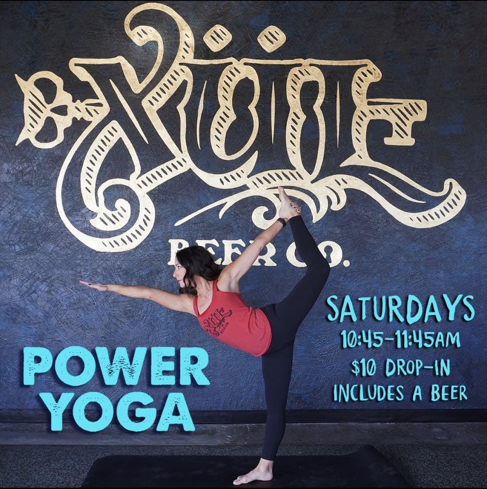 Yoga pose in front of our logo wall in the taproom
